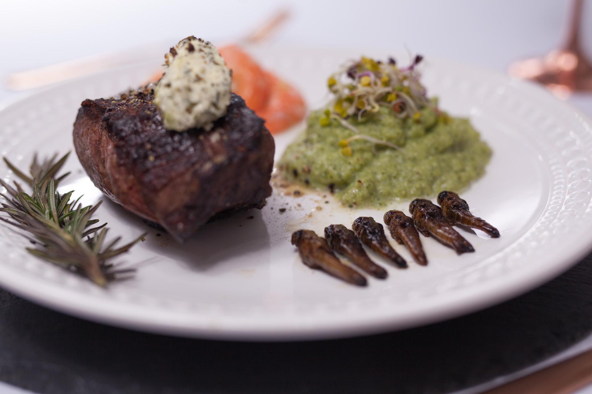Steakgericht mit Rindersteak, Riesengarnelen, Wanderheuschrecken und Brokkoli-Stampf.